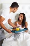 Человек принося завтрак женщины в кровати на подносе Стоковое Изображение