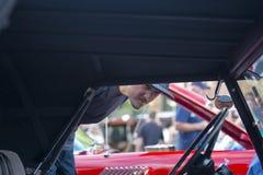 Человек при борода смотря винтажный автомобиль на ретро выставке автомобиля Стоковое Фото