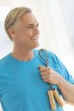 Человек при веревочка скачки смотря прочь в спортзале Стоковое Изображение