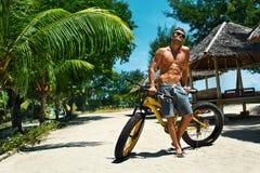 Человек при велосипед спорта ослабляя на тропическом пляже в лете Стоковые Фотографии RF