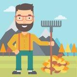 Человек при грабл стоя около кучи листьев осени Стоковые Фото