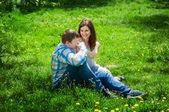 Человек при женщина сидя на траве и ем целует ее руку Стоковые Фото