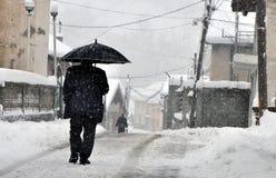Человек при зонтик идя вниз с улицы Стоковые Фотографии RF