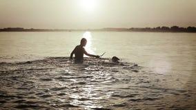 Человек при маленький щенок бигля околпачивая вокруг в волнах захода солнца океана видеоматериал