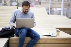 Человек при мобильный телефон показывая к умелому главному исполнительному директору используя портативный компьютер и беспроволо Стоковая Фотография RF