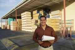 Человек при доска сзажимом для бумаги стоя перед фабрикой тимберса Стоковая Фотография