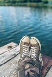 Человек при пересеченные ноги ослабляя на пристани речного берега Стоковые Фото