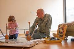 Человек при ребенок ремонтируя журнальный стол Стоковое фото RF