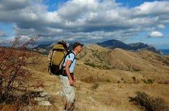Человек при рюкзак смотря море от горного склона Стоковое Фото