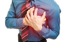 Человек при сердечный приступ отжимая руки к комоду стоковая фотография rf