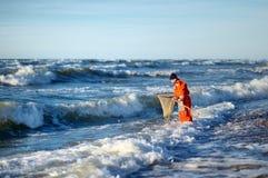 Человек при сеть посадки ища янтарь на море Стоковые Изображения