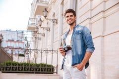 Человек при старая винтажная камера фото стоя в городе стоковое фото