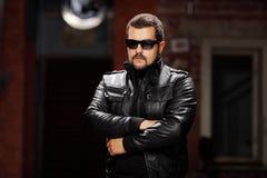 Человек при стекла нося черную куртку и представлять Стоковая Фотография