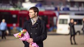 Человек при цветки ждать его женщину в городе видеоматериал