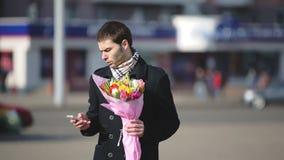 Человек при цветки ждать его женщину в городе сток-видео