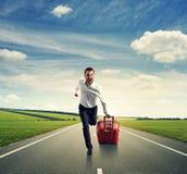 Человек при чемодан бежать на дороге стоковые изображения rf