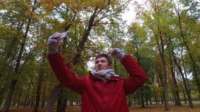 Человек при smartphone принимая видео на парк осени акции видеоматериалы
