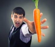 Человек пробуя достигнуть морковь стоковое изображение rf