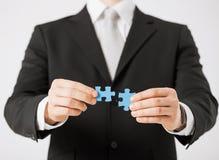 Человек пробуя соединить части головоломки Стоковые Фотографии RF