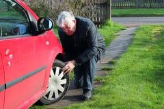 Человек проверяя автошины или покрышки автомобиля. Стоковое Изображение