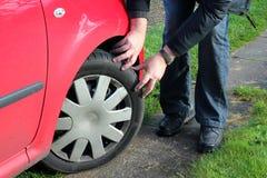 Человек проверяя автошины или покрышки автомобиля. Стоковая Фотография RF