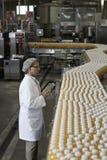 Человек проверяя бутылки апельсинового сока на заводе по розливу Стоковые Изображения