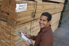 Человек проверяя пиломатериал в складе стоковое изображение rf