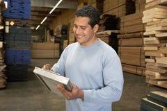 Человек проверяя пиломатериал в складе стоковые фотографии rf