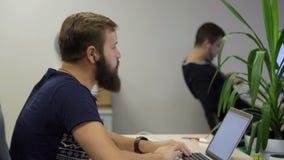 Человек программируя на компьтер-книжке видеоматериал
