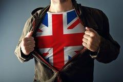 Человек протягивая куртку для того чтобы показать рубашку с флагом Великобритании Стоковая Фотография RF