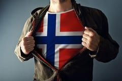 Человек протягивая куртку для того чтобы показать рубашку с флагом Норвегии стоковое изображение rf