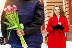 Человек прячет цветки за его назад для его подруги Красивые молодые пары идя совместно через улицы города Стоковая Фотография