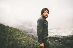Человек путешественника идя на туманные горы Стоковое Фото