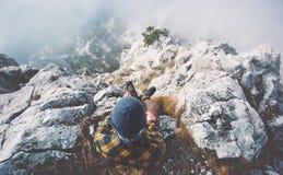 Человек путешественника ослабляя самостоятельно на саммите скалистой горы Стоковая Фотография RF