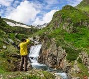 Человек путешественника принимая фото большого водопада в Georgia Стоковые Фотографии RF