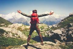 Человек путешественника при поднятые руки рюкзака скача Стоковое фото RF