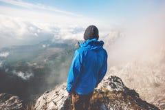 Человек путешественника самостоятельно на саммите горы над облаками Стоковое Фото