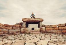 Человек путешественника сидя на каменном дольмене Стоковое Фото