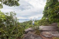 Человек путешественника стоя на большом камне держа его руку поднимающий вверх и видит l Стоковая Фотография RF