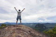 Человек путешественника стоя на большом камне держа его руку поднимающий вверх и видит l Стоковая Фотография