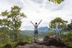 Человек путешественника стоя на большом камне держа его руку поднимающий вверх и видит l Стоковое Изображение