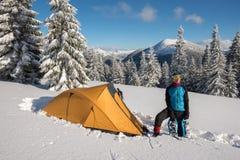 Человек, путешественник с snowshoes ослабляет около шатра Стоковые Фото