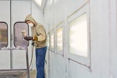 Человек работает в краск-распыляя будочке, крася детали автомобиля стоковые фотографии rf