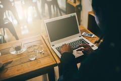 Человек работая на компьтер-книжке пока сидящ Стоковое фото RF