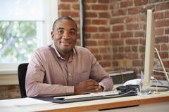 Человек работая на компьютере в современном офисе Стоковая Фотография