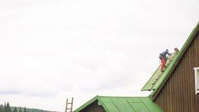 Человек работая на крыше, краска Sandering стоковая фотография rf