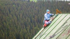 Человек работая на крыше, проверяя шестерню безопасности стоковая фотография rf