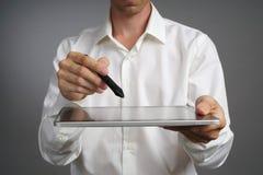 Человек работая на таблетке с грифелем Стоковые Фото
