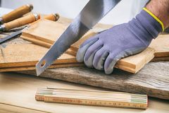 Человек работая с ручной пилой Стоковые Изображения