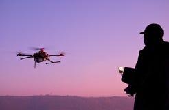 Человек работая трутня с дистанционным управлением Темный силуэт снова Стоковое фото RF